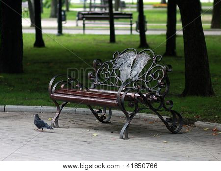 Metal Forged Bench In authumn Park With A Pair Of Lovers In Heart