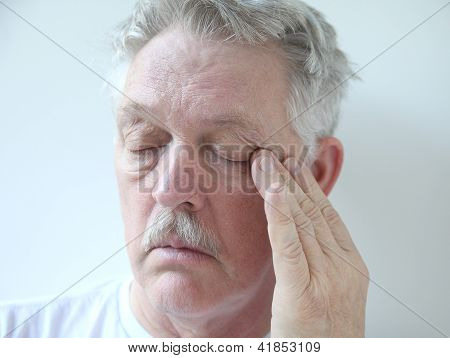 older man with eye fatigue
