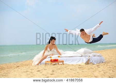 Happy groom flying on bed to his sweetheart on the beach
