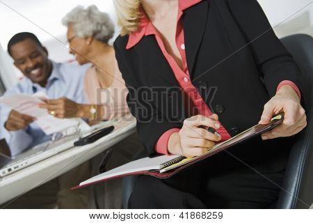 Cropped image of female financial adviser holding file with couple sitting in background