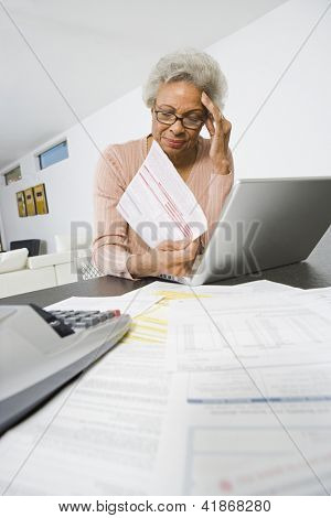 Upset African American senior woman with hand on head worrying about home finances