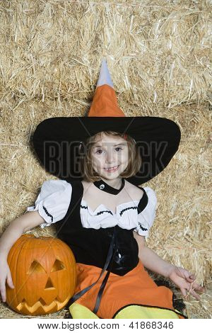 Portrait of a cute little Caucasian girl sitting with pumpkin in Halloween outfit