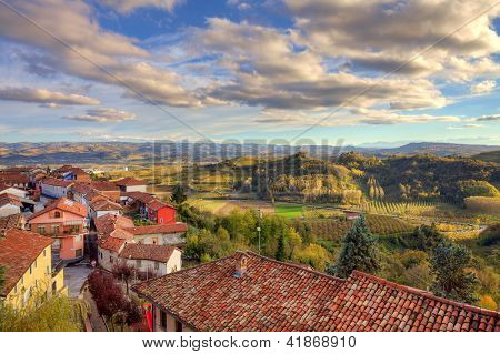 View on red tiled roofs of small town among hills and meadows under beautiful sky at sunset in autumn in Piedmont, Italy.