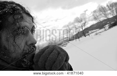 Black and white portrait of frozen homeless man looking desperate