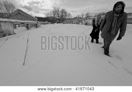 Black and white image of homeless struggling couple walking in winter time walking
