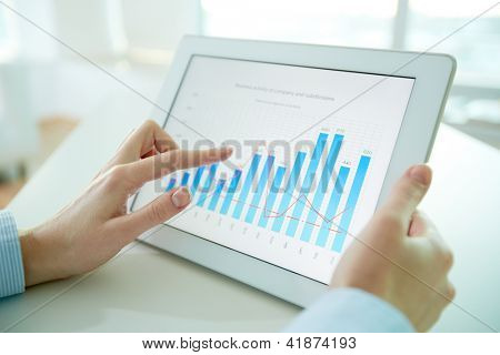 Female worker analyzing financial results with the help of a digital pad