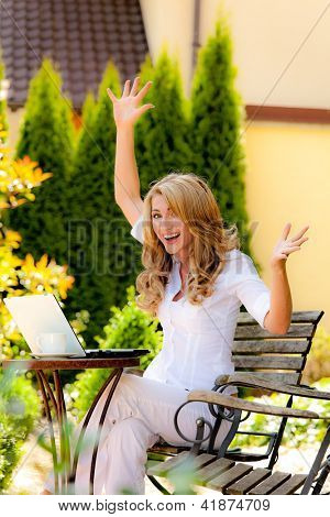 successful, laughing woman with laptop in garden