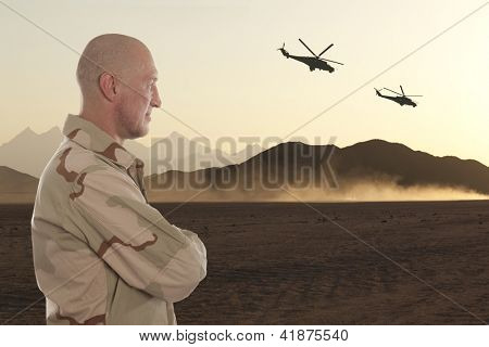 Marine amid the mountains of Afghanistan and helicopters