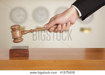 Judge holding gavel against the clock