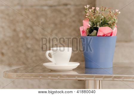 Coffee cup and saucer on table besides flower pot