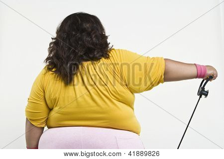 Rear view of an obese woman exercising isolated over white background