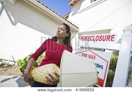 Sad  woman carrying lamp while moving out of the house