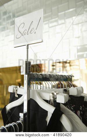 """Roupas penduradas em um rack em loja de varejo de moda com sinal de """"Venda"""" na placa"""