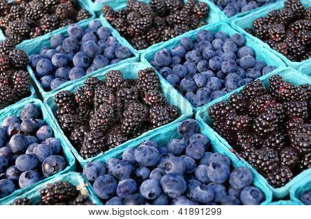 Blackberries and blueberries at an outdoor farmers' market.