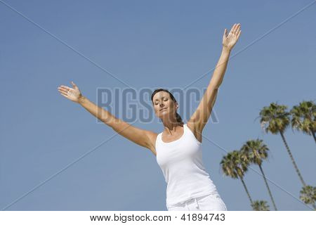 Low angle view of woman in white sportswear meditating with arms outstretched