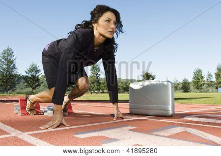 Mulher de negócios confiante na posição inicial de uma pista de corrida com maleta contra o céu