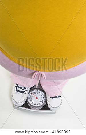 Low section of an obese woman measuring weight on weighing machine