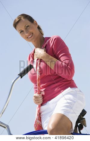 Low angle view of a woman in casual wear sitting on a bike against clear sky