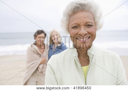 Portrait of happy African American senior woman with friends at beach