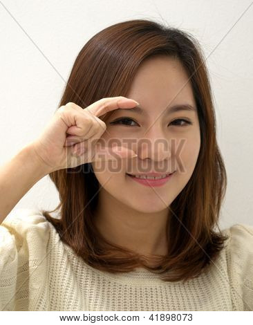 An adult female hand sign the message of something small