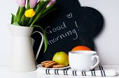 stock photo of jug  - bouquet of tulips in a white jug morning coffee fruit and chalk board with the inscription on a white background - JPG