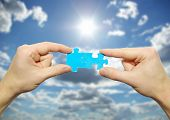 picture of reunited  - puzzle in hand isolated on sky background - JPG