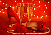 Photo of beautiful red romantic still life, two glass of champagne, shoes on high heels, luxury whit