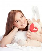 Picture of happy woman laying down in the bed, girl enjoying romantic present, soft bear and red han
