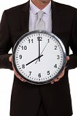 pic of beheaded  - A cropped picture of a businessman holding a clock - JPG
