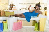 African American woman lying on sofa in a lavish clothing store with shopping bags on floor poster