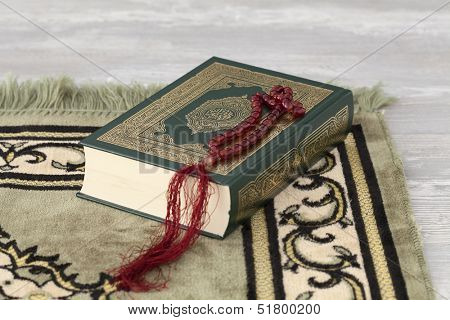 The Quran and the prayer beads on a carpet
