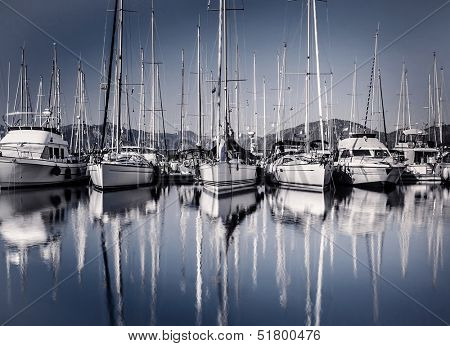 Sailboat harbor in evening, many luxury moored sail yacht in the port, ship mast reflected in water, marina in European city, summer holidays