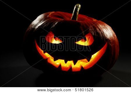 Halloween pumpkin with scary face on black background