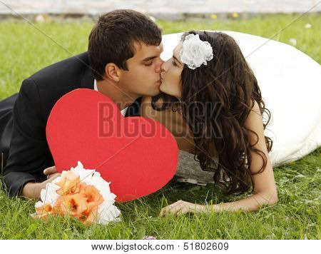 Wedding, beautiful young bride lying together with groom in love on green grass and kissing, park summer outdoor