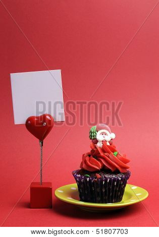 Red Santa Christmas Festive Cupcake In Purple Polka Dot Wrapper On Green Plate Against A Red Backgro