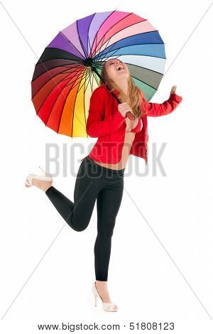Vivacious stylish young woman running with a rainbow umbrella over her head laughing joyfully and kicking her leg in the air, isolated on white