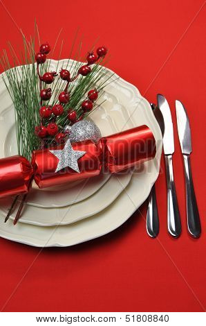 Modern Bright Red Christmas Table Setting With Cracker And Baubles, Plates And Cutlery, On A Red Tab