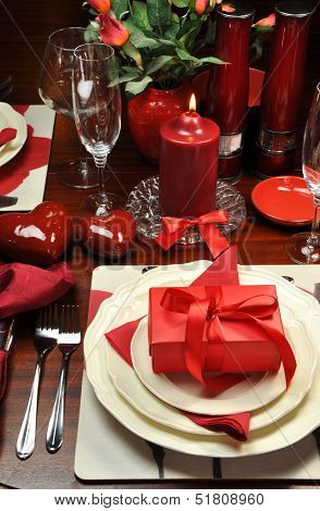 Red Valentine Romantic Dinner For Two Table Setting With Gift, Candle And Hearts - Vertical.