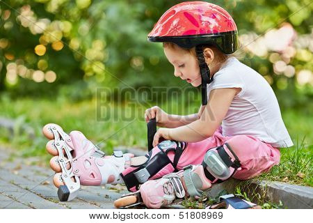 Little girl in protective equipment and rollers fastens knee-pad, sitting on curb of walkway in park.