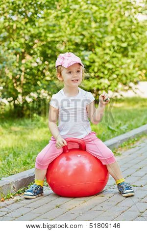 Smiling little girl sits on red ball for jumping on walkway in park, holding green leaf in her hand
