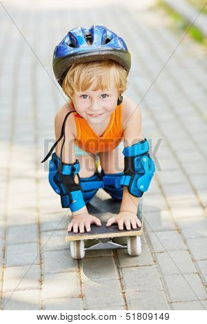 Little boy in protective helmet stands on knees and hands on skateboard
