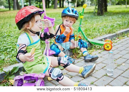 Children scooterists rest sitting on curb of walkway in park, focus on girl