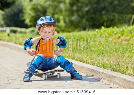 Little skateboarder sits on park alley on skateboard with arms akimbo