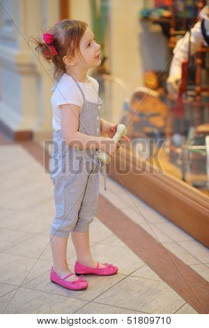 Little cute girl holds toy bone and looks at shop window in mall.