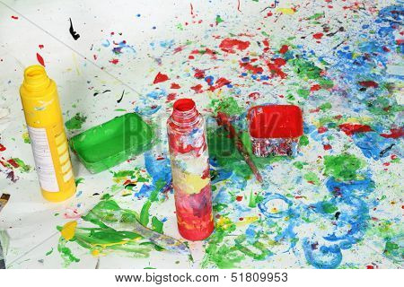 Open a bottle of paint on the floor with multicolored stains of paint