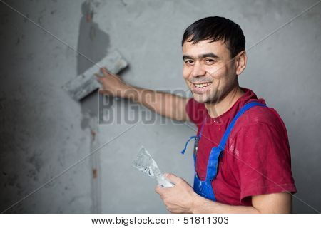 A smiling worker with spatula in workwear makes repairs smears on the wall putty