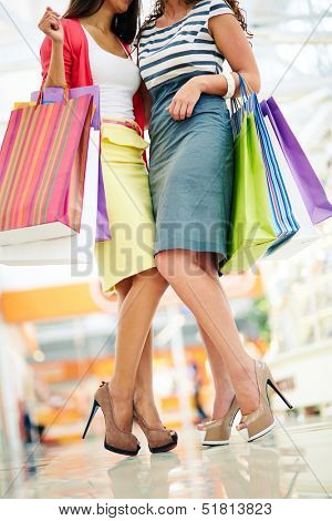 Legs of shoppers with paperbags in trade center