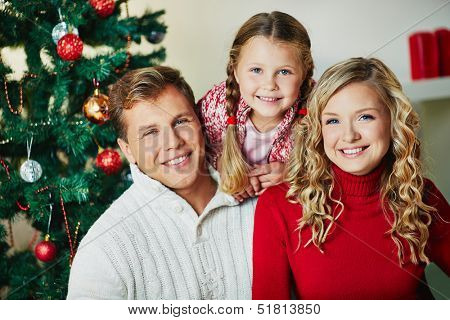 Portrait of happy family looking at camera on Christmas day