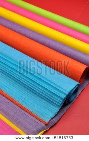 Brihgt Rainbow Colored Reams (rolls) Of Tissue Wrapping Paper On A Red Background.