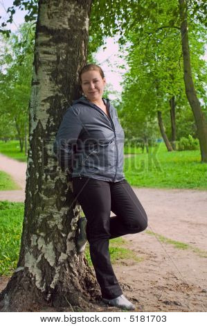 Young Woman Stands Near The Birch In Forest